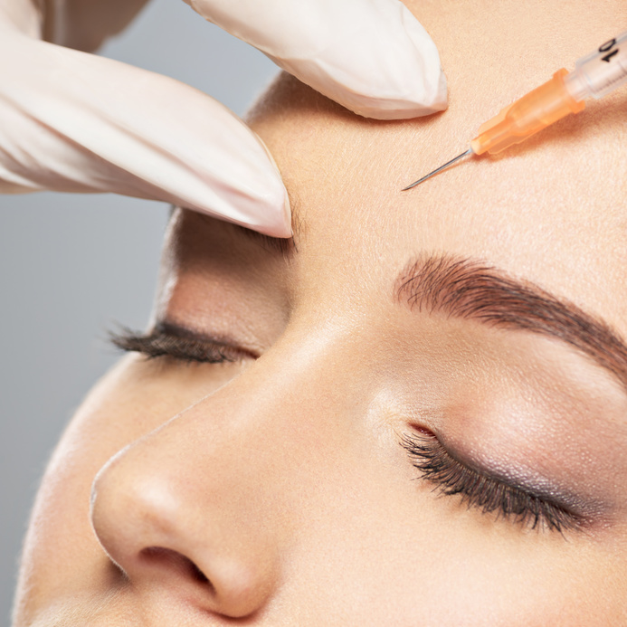 Woman getting cosmetic injection of botox near eyes