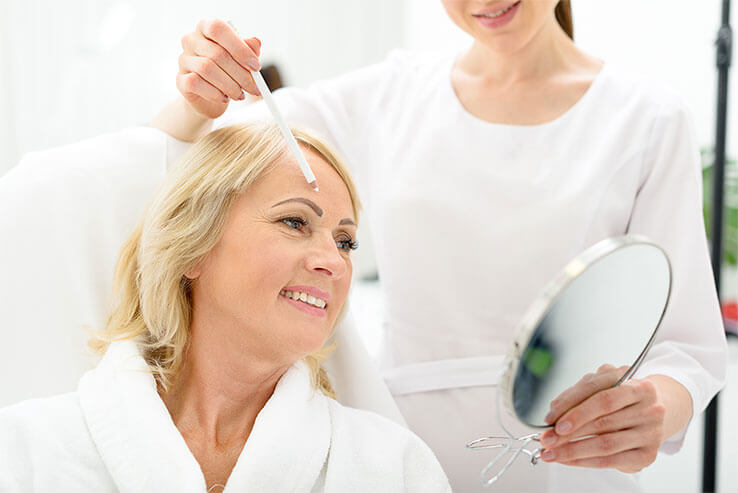 Frau bekommt Reinigung vor Gesichtsbehandlung